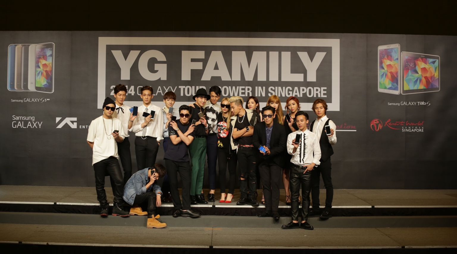 A group photo of the YG Family artistes at the Samsung press conference, posing with the latest Samsung devices
